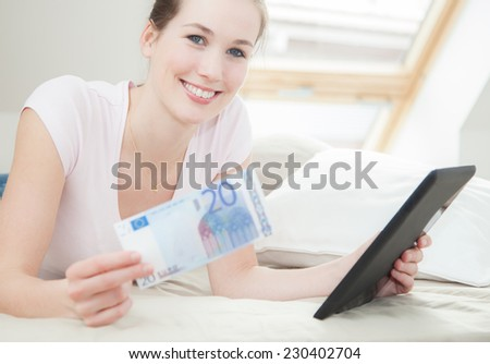 Attractive young woman holding 20 euro and tablet - stock photo