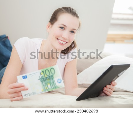Attractive young woman holding 100 euro and tablet device - stock photo