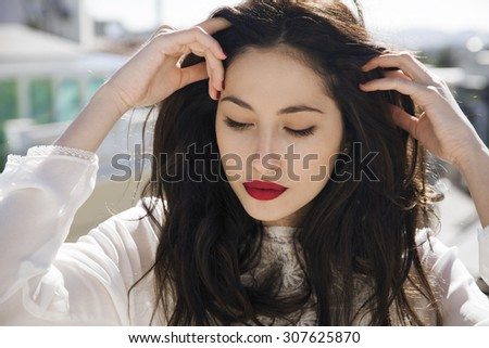 attractive young woman holding her healthy and shiny hair.Hair and makeup.  Horizontal shot. - stock photo