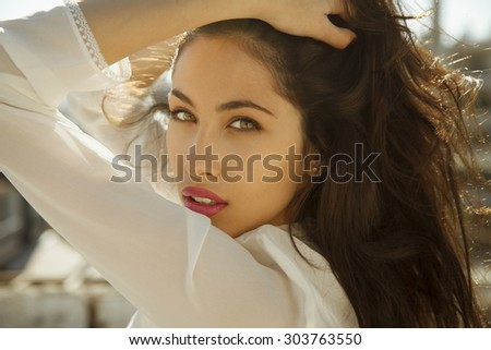 attractive young woman holding her healthy and shiny hair. Horizontal shot. - stock photo