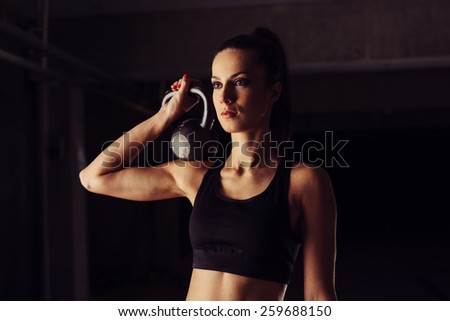 Attractive young woman holding kettlebell on her shoulder - stock photo