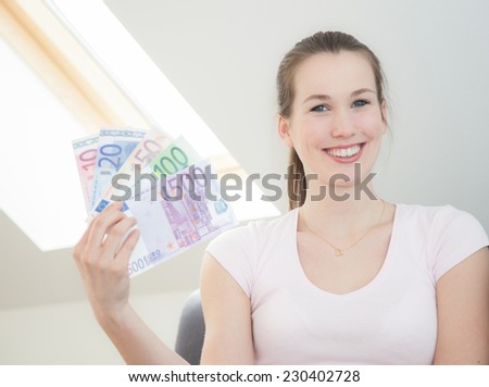 Attractive young woman holding lots of euro notes. - stock photo