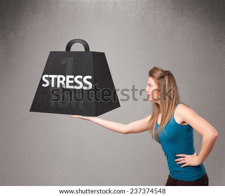 Attractive young woman holding one ton of stress weight - stock photo