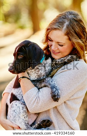 attractive young woman holding puppy in arms smiling