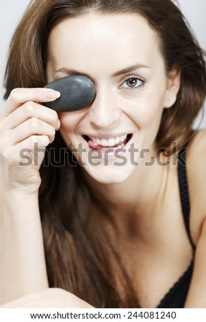 Attractive young woman holding spa treatment warm stones relaxing on a bed in black underwear - stock photo