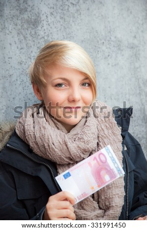 Attractive young woman holding ten euro note