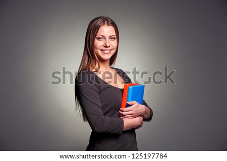attractive young woman holding two books and looking at camera over dark background - stock photo