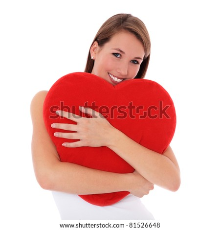 Attractive young woman hugging heart-shaped pillow. All on white background. - stock photo