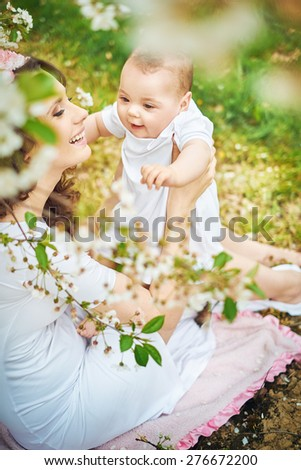 Attractive young woman hugging her baby - stock photo