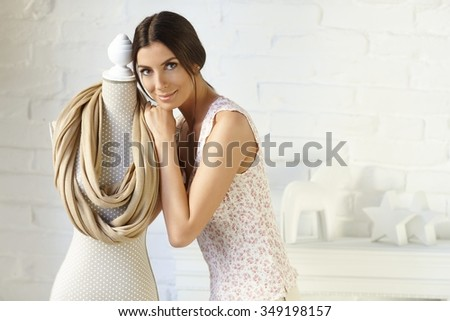 Attractive young woman hugging mannequin with favourite scarf, smiling, looking at camera.