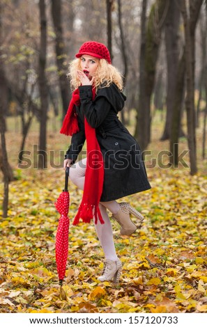 attractive young woman in a autumn fashion shot.Beautiful fashionable young girl with red umbrella , red cap and red scarf in the park