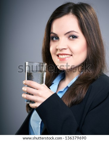 Attractive young woman in a black jacket. Woman holding a glass of mineral water. On a gray background