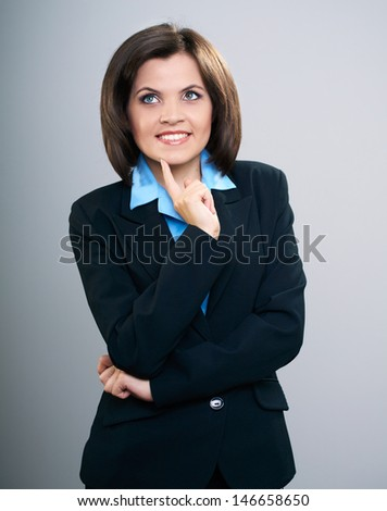 Attractive young woman in a black suit. Holding her finger on her chin. Looking into the upper-right corner. Isolated on a gray background - stock photo