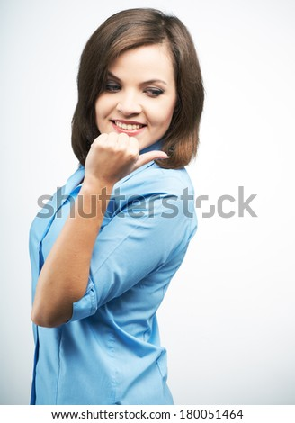 Attractive young woman in a blue blouse. Indicates her finger back. On a gray background - stock photo