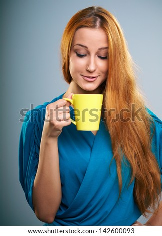 Attractive young woman in a blue dress. Holds a yellow cup. Isolated on a gray background