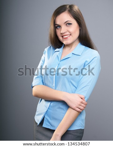 Attractive young woman in a blue shirt and a gray skirt. On a gray background
