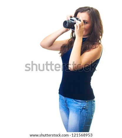 Attractive young woman in a blue shirt and blue jeans holding a camera. Isolated on white background