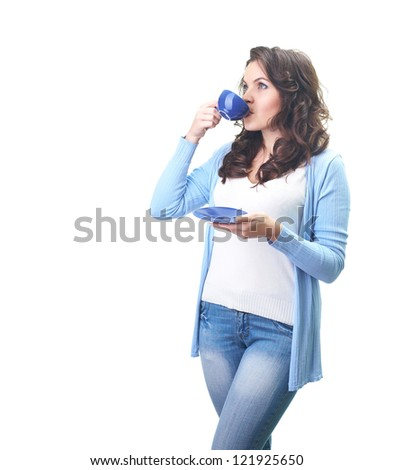 Attractive young woman in a blue shirt drinking from a blue cup. Isolated on white background