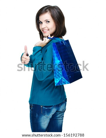 Attractive young woman in a blue shirt. Holds the gift bag and showing thumbs up. Isolated on white background
