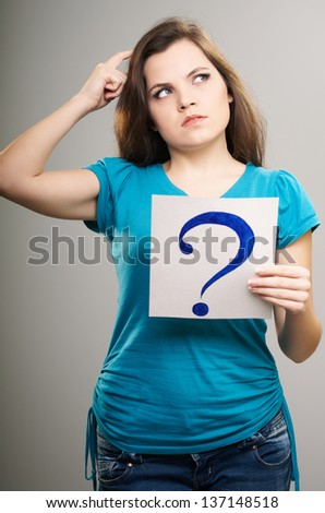 Attractive young woman in a blue shirt. Woman holds a poster with a big question mark. Thoughtful. On a gray background - stock photo