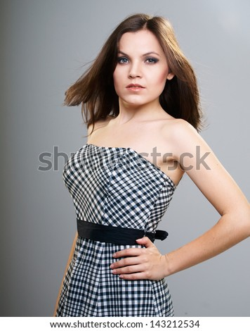 Attractive young woman in a checkered dress. Isolated on a gray background