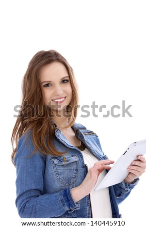 Attractive young woman in a denim jacket standing using a handheld tablet computer, isolated on white