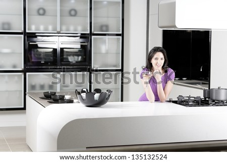 Attractive young woman in a dinner dress holding a glass of wine in her kitchen. - stock photo
