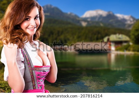attractive young woman in a dirndl in the alps - stock photo