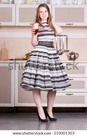 Attractive young woman in a dress holding a glass of wine in her kitchen.