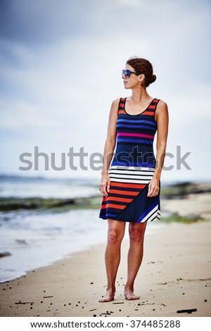 attractive young woman in a dress walking on a beach - stock photo