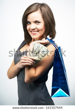 Attractive young woman in a gray business dress. Holds a gift bag and money. On a gray background - stock photo