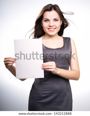 Attractive young woman in a gray business dress. Holds a poster. On a white background