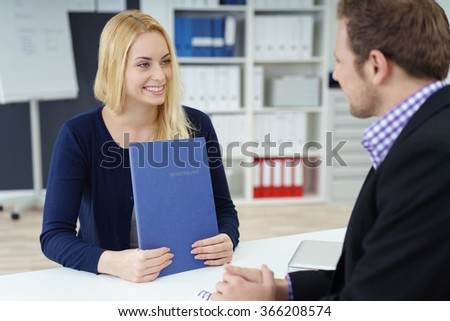 Attractive young woman in a job interview with a businessman sitting at his desk holding her curriculum vitae smiling warmly - stock photo