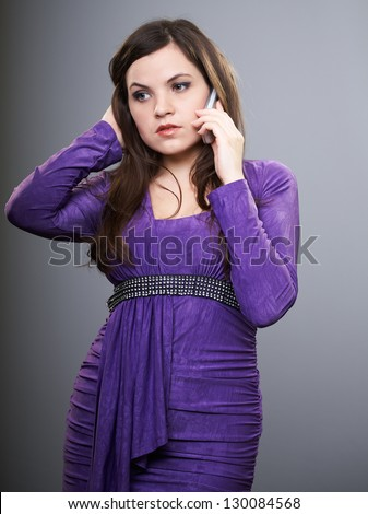 Attractive young woman in a lilac dress. Woman talking on mobile phone. Looking down. On a gray background