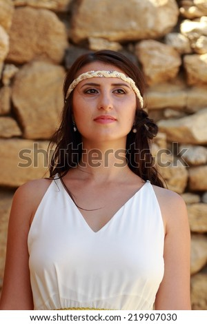 Attractive young woman in a long white wedding dress with beautiful hairstyle on background of an old stone wall as the ancient Greek goddess - stock photo