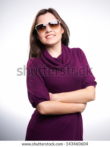 Attractive young woman in a red dress and sunglasses. Looking to the right. On a white background - stock photo