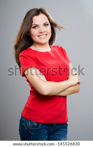Attractive young woman in a red shirt and jeans. Standing with folded hands. Isolated on a gray background - stock photo