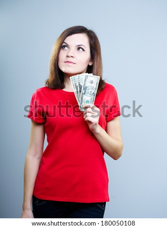 Attractive young woman in a red shirt. Holding dollars and looking in the upper-right corner. On a gray background - stock photo