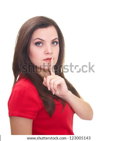 Attractive young woman in a red shirt holding her finger near her lips, showing a sign of silence. Isolated on white background