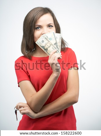 Attractive young woman in a red shirt. Holds dollars and keys. On a gray background