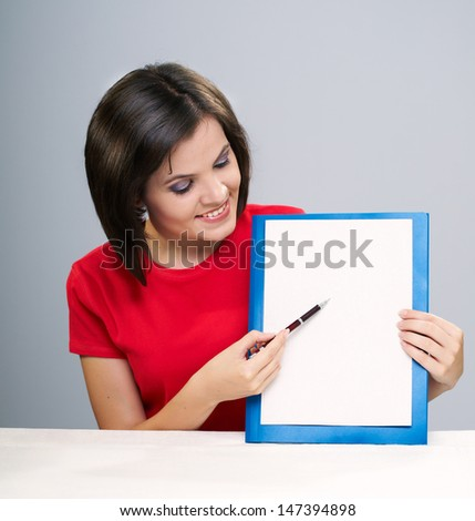 Attractive young woman in a red shirt sitting at the table. Woman holds a poster and show something. Isolated on a gray background - stock photo