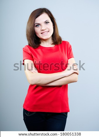 Attractive young woman in a red shirt. Stands with folded hands. On a gray background - stock photo