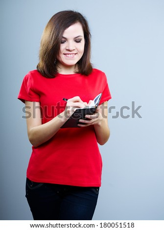 Attractive young woman in a red shirt. Writes in a notebook. On a gray background