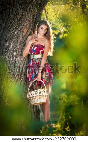 Attractive young woman in a summer fashion shot. Beautiful fashionable young girl with straw basket in park near a tree. Brunette woman posing in forest in a sunny day, outdoor shot - stock photo