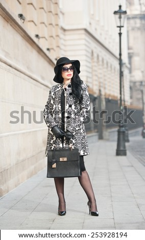 Attractive young woman in a winter fashion shot. Beautiful fashionable young girl in black  posing on avenue. Elegant brunette with hat, sunglasses and handbag in urban scenery. - stock photo