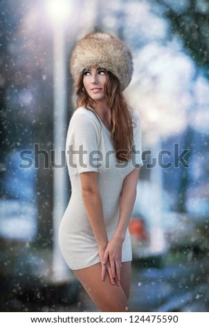 Attractive young woman in a winter fashion shot.Winter wild girl on snow.Winter Girl with beautiful make up, and snow flake, forest background.Portrait of sexy woman - stock photo