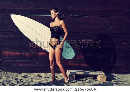attractive young woman in bikini and black top holding surfboard on sandy beach by wooden wall full body shot - stock photo