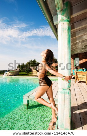 attractive young woman in bikini by the pool - stock photo