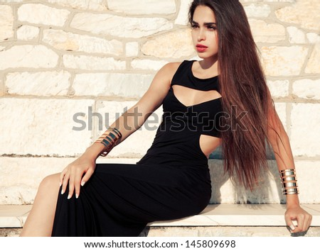 Attractive young woman in black dress and golden bracelets posing against old stone wall. soft sunny colors. outdoors horizontal shot. - stock photo