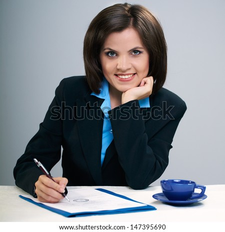 Attractive young woman in black jacket sitting at the table. Sign documents. Isolated on a gray background